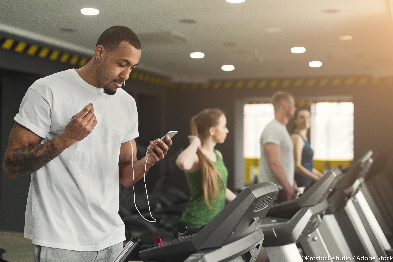 Black sporty man on treadmill in fitness club